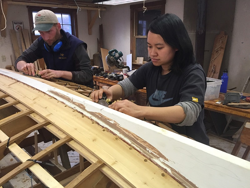 two apprentices work on the keel of a dinghy