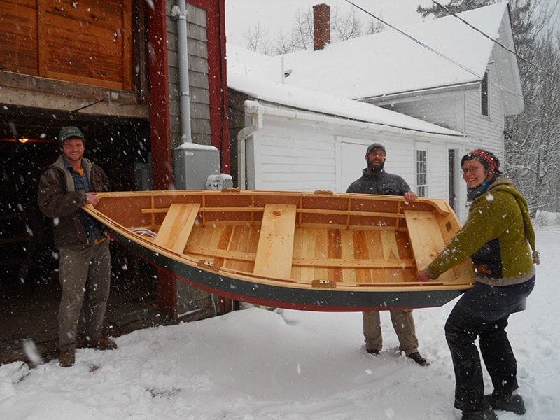 carrying a new skiff in the snow