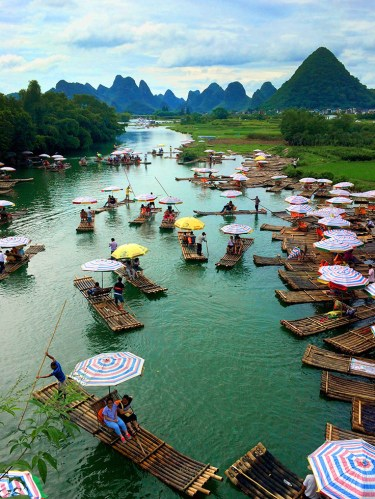 Tourist taking bamboo raft tours on the Yulong River at the Yulong Bridge in Yangshuo, China