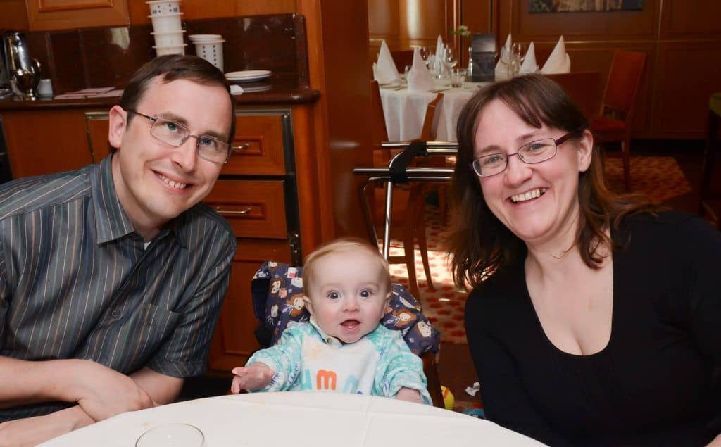 Baby whose reflux has cleared up sitting between his mum and dad