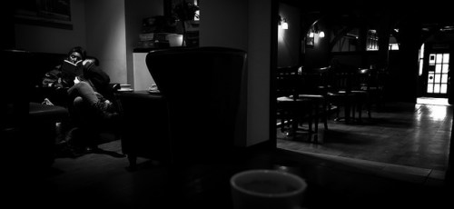 woman in a chair in a dark cafe reading a book