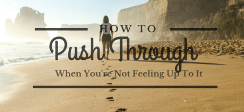 woman walking on the beach with footprints how to push through when you're not feeling up to it