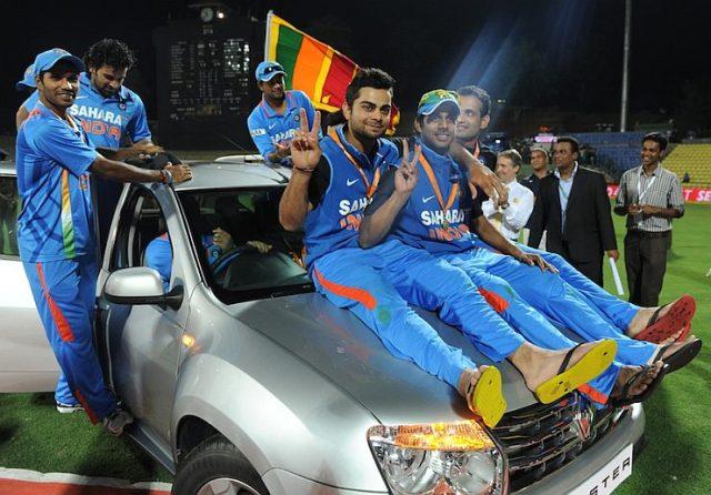 Indian cricketer Virat Kohli (C) sits wi