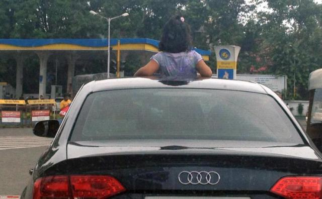 Kid sticking head out of car sunroof