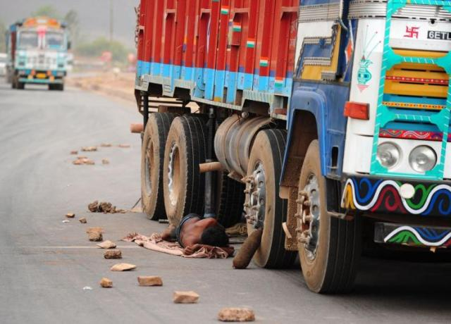 Truck driver resting under truck in India