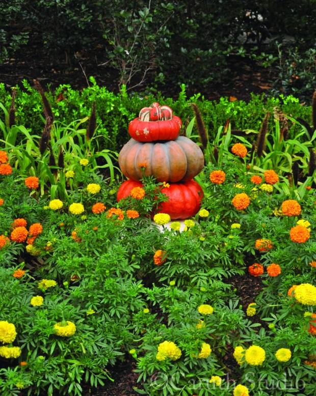 pumpkin stack in flower bed