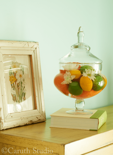 Flowers and produce in apothecary jar