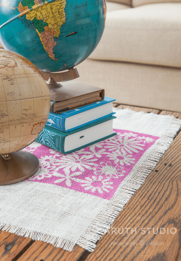 pink and white Burlap runner under blue books and two world globes