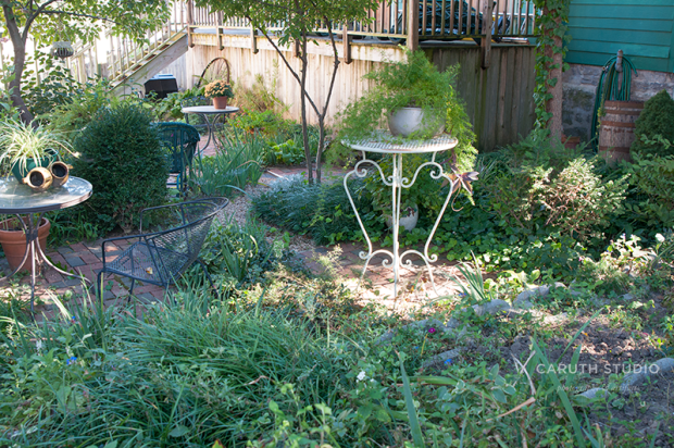 Pocket garden with green foliage and bistro set
