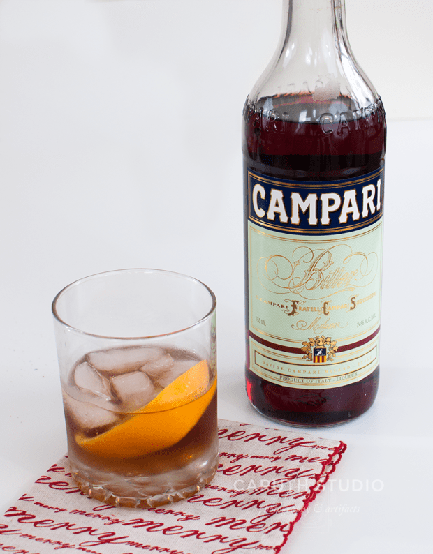 Bijou cocktail in a tumbler on a christmas napkin with Campari bottle in the background