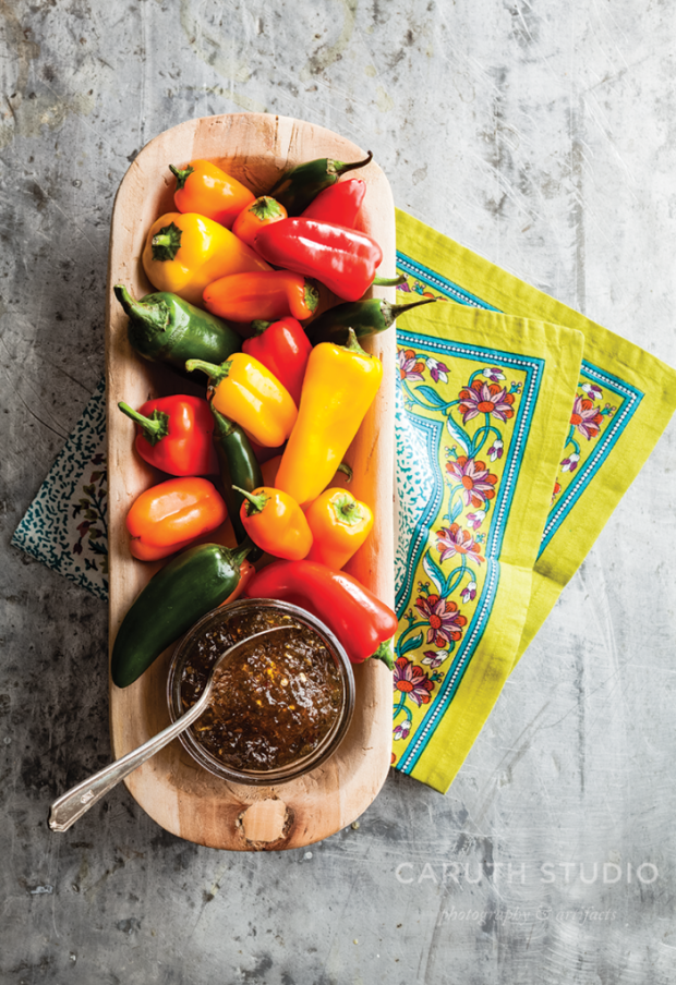 Pepper Jelly on wooden bowl and peppers with a fiesta napkin