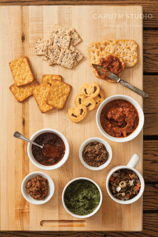 Condiments and sauces on butch block with assorted crackers