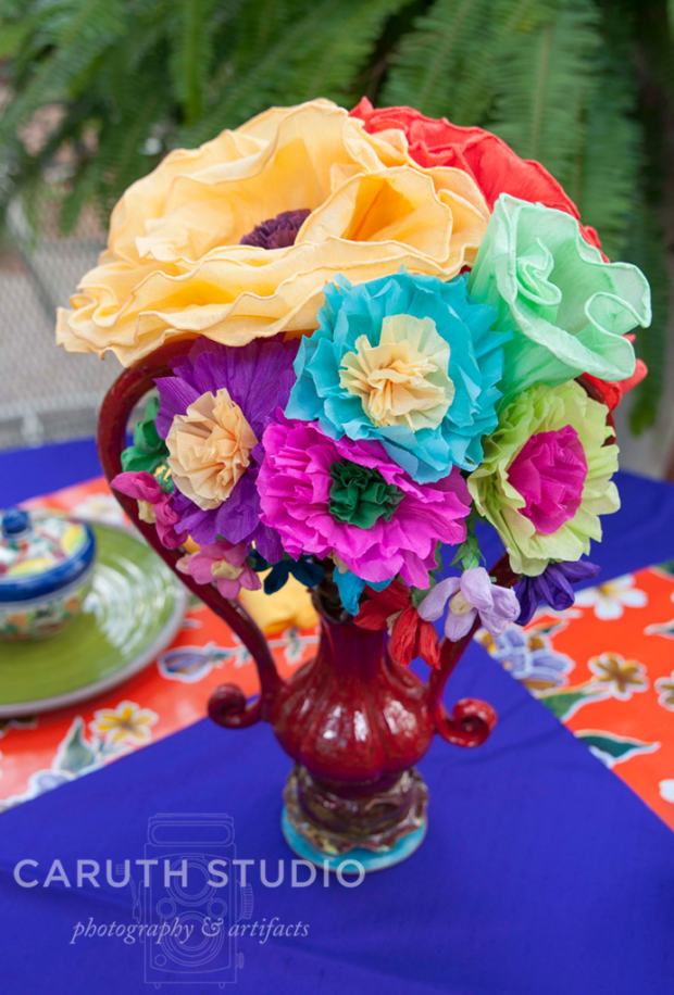 Paper flowers in vase on festive table clothe