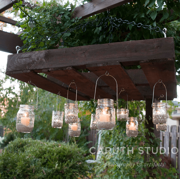 Votives hanging off pallet which hangs off vine covered pergola