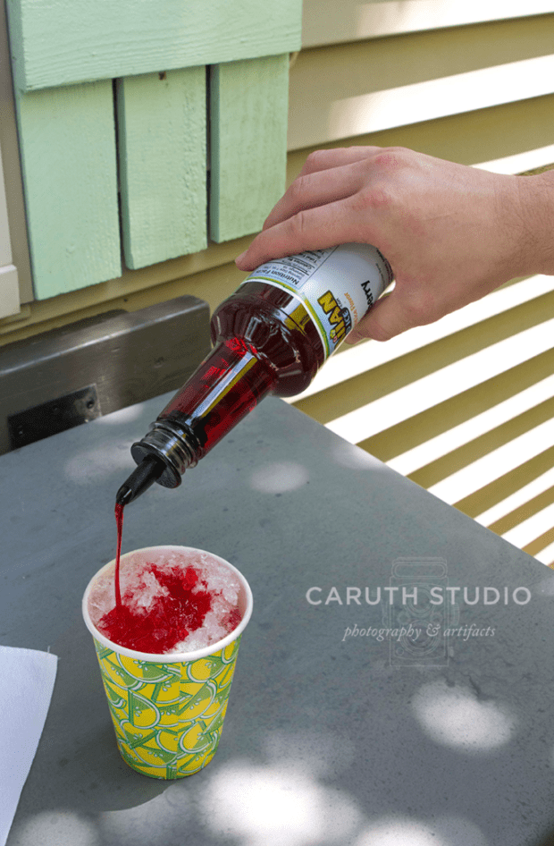 pouring store-bought syrups on shaved ice