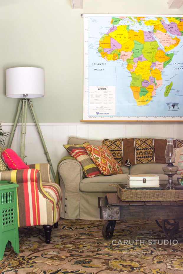 couch, chair, tripod lamp, and wooden coffee table below the world map on the wall