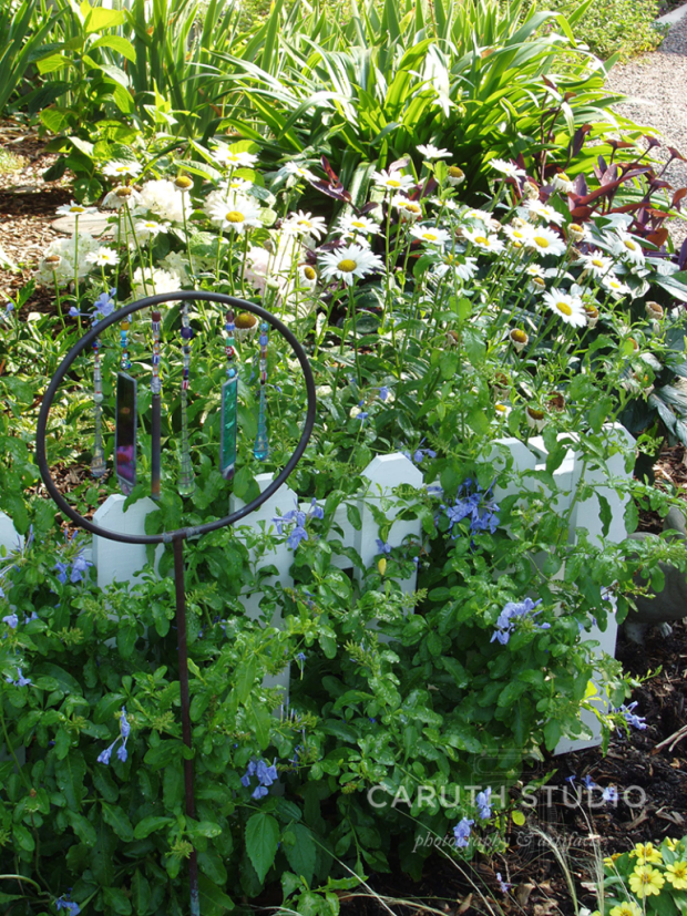 Wind chimes in bed of daisies and plumbago