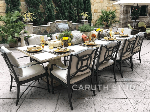 ten person table with fall themed decoration and place settings on an outdoor patio