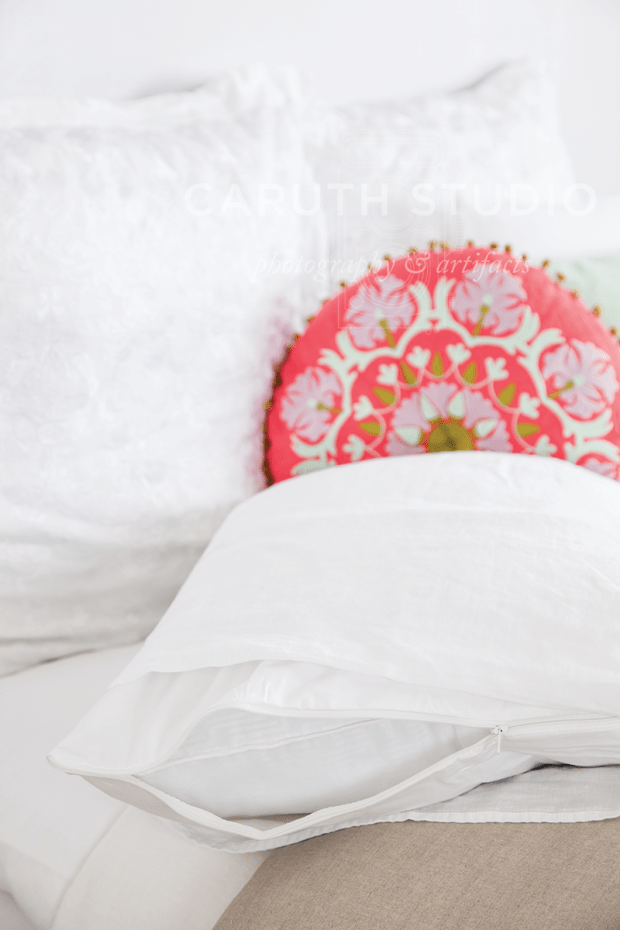 pink and white circular decorative pillow nestled among white sheets and pillows - camera focus on the white pillow cover