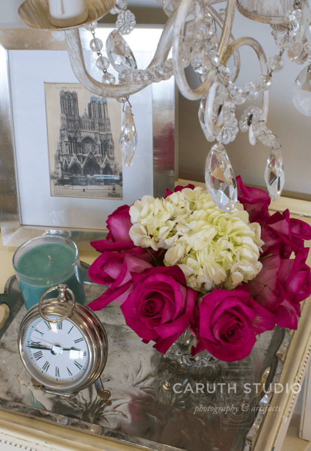 Romantic nightstand tabletop jeweled clock, vase of flowers in white and pink, a teal candle and a silver framed picture