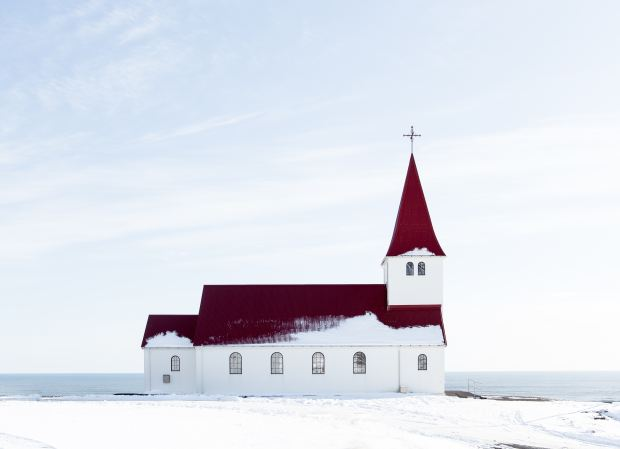 white church with red roof with sea in the background and a snowy foreground