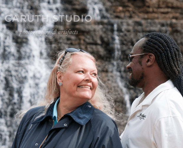Debra and Narvas smiling at each other in front of a waterfall