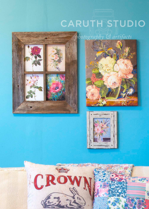 hung floral artwork on the blue wall above the couch