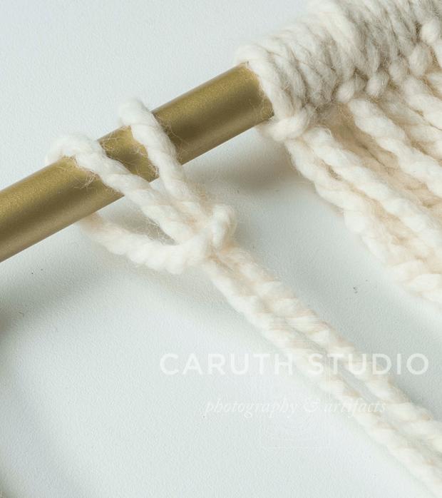Lark's head knot on gold curtain rod