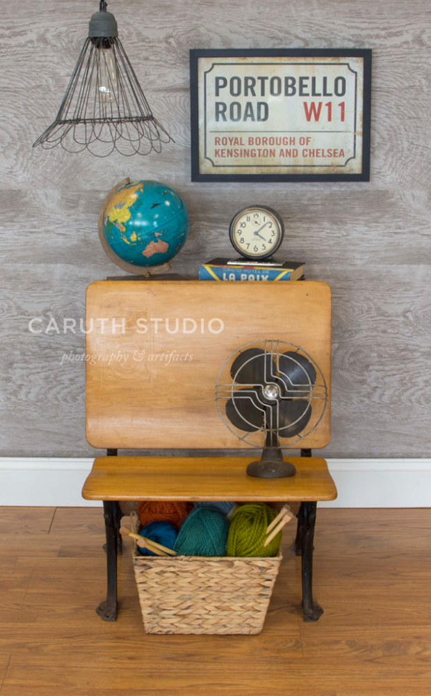vintage nightstand with globe, clock, stack of books on back, a vintage fan on the seat and a basket below, and pendant wire basket light hanging above and a framed Portobello Road sign hung on the wall