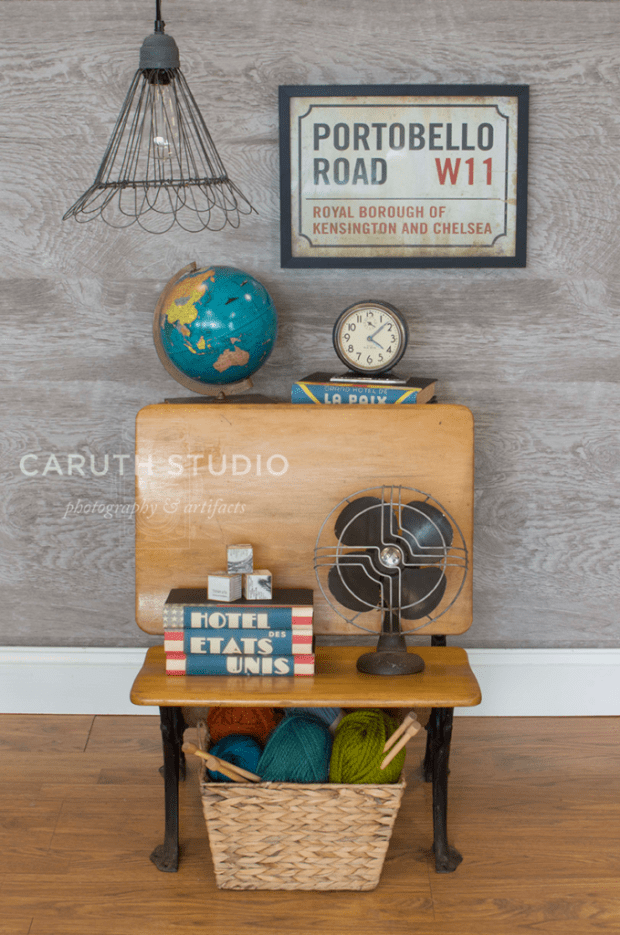 vintage wooden desk nightstand with clock, fan, globe and stacks of books with a yarn basket beneath