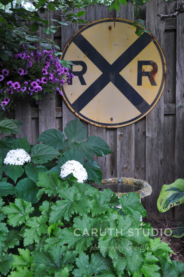 rail road sign hanging on a fence behind hydrangeas and petunias