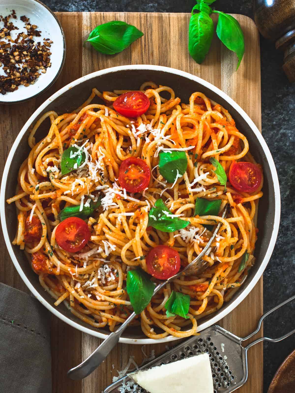 Spaghetti pasta in a brown dish with tomatoes