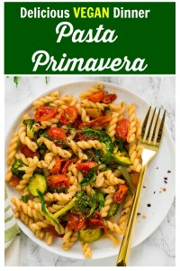 Pasta primavera with roasted vegetables on a white plate.