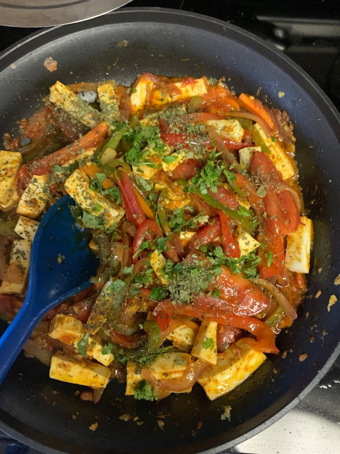 Paneer and veggies mixed together in a pan