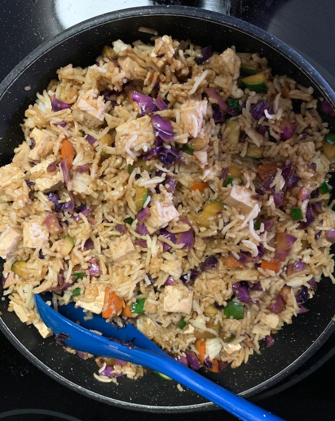 Tossing the rice with the sauce and veggies.