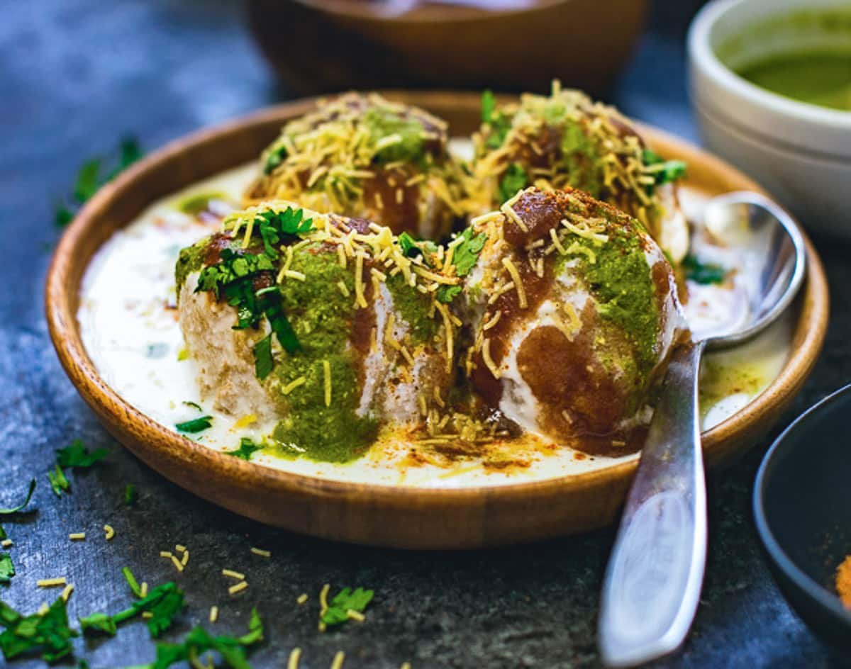 Dahi vada with on a plate with a spoon