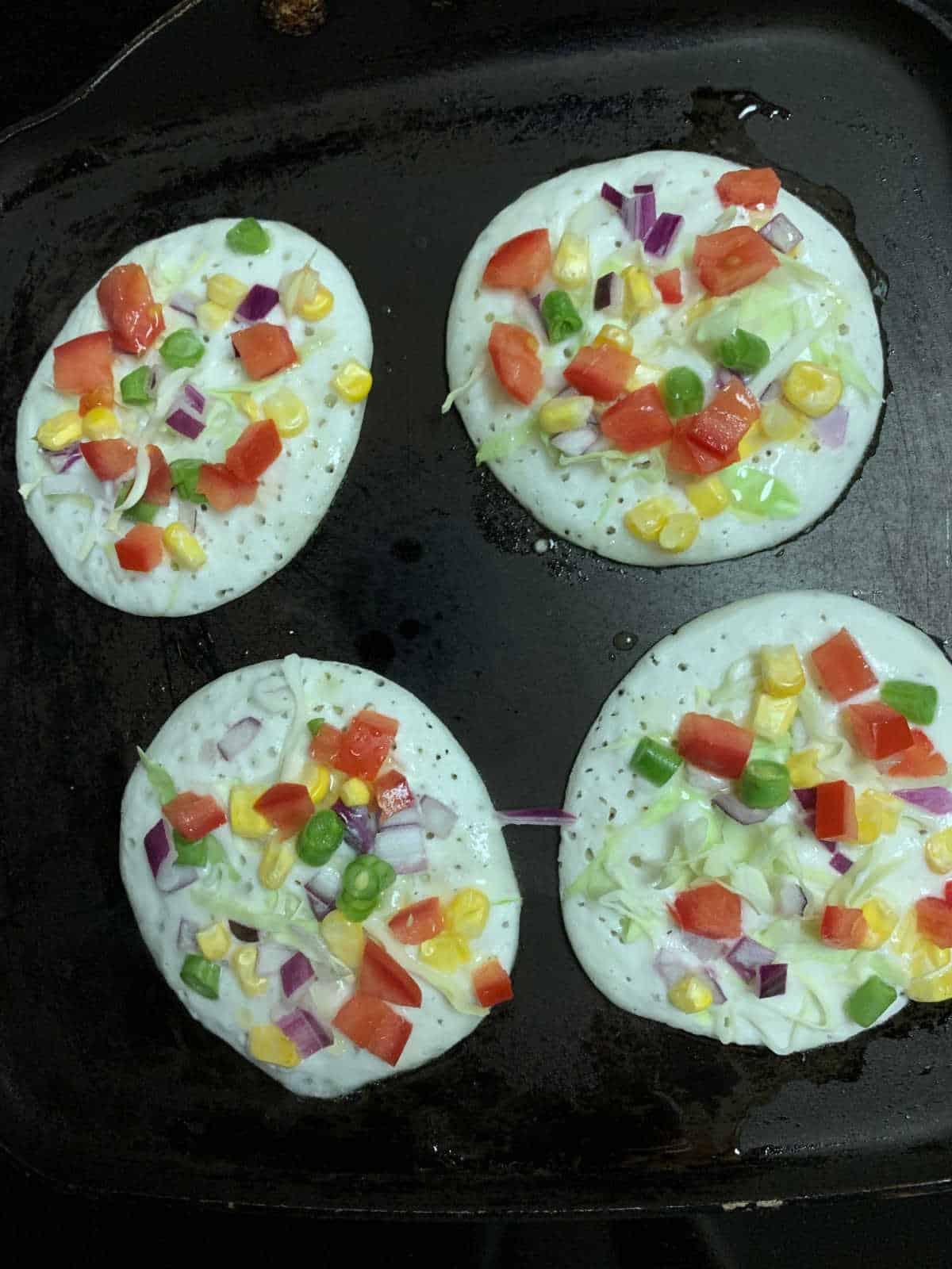 Mini uttapams cooking on the tawa.