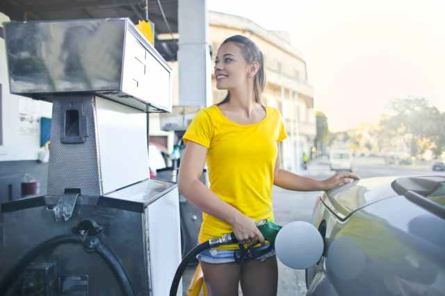 woman in yellow shirt while filling up her car with gasoline