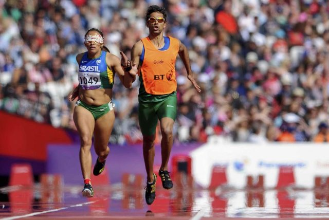 LONDON, ENGLAND - SEPTEMBER 03: Terezinha Guilhermina of Brazil and her guide Guilherme Soares de Santana compete in the Women's 400m T-12 on day 5 of the London 2012 Paralympic Games at Olympic Stadium on September 03, 2012 in London, England. (Photo by Buda Mendes/LatinContent/Getty Images)