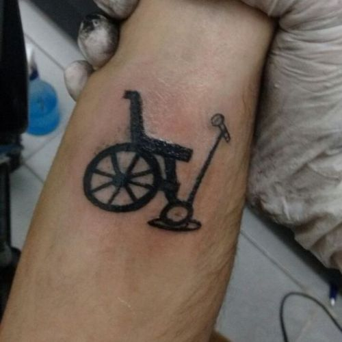 A imagem está no formato quadricular. Nela contém o punho do comediante Paulo Fabião mostrando sua tatuagem que é um desenho de uma cadeira de rodas com um tripé segurando um microfone na frente. Fim da descrição.