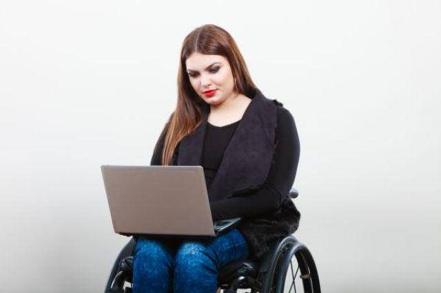 A imagem está no formato retangular na horizontal. Nela contém uma jovem sentada em uma cadeira de rodas digitando concentrada em um notebook que está apoiado em suas pernas. Fim da descrição.