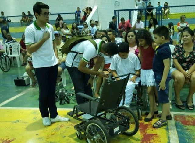 Alunos demonstram como a cadeira funciona para uma criança deficiente física (Foto: Ana Eliza)