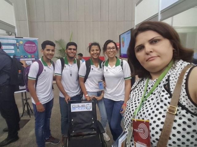 Professora e alunos apresentam o projeto de cadeira roda controlada por aplicativo em feiras de ciência (Foto: Arquivo pessoal)