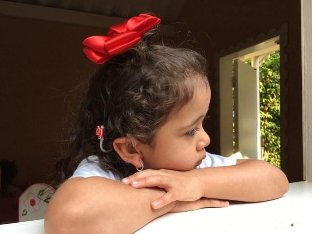 Com implante coclear, a pequena Júlia pode desenvolver a audição e, por consequência, a fala (Foto: Kátia Fugiwara de Oliveira/Arquivo pessoal )
