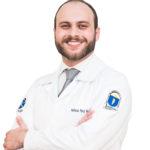 Descrição da imagem #PraCegoVer: Imagem no formato quadrado. Nela, está o doutor Matheus. Ele é um homem de pele branca e com cabelos e barba castanhos. Ele usa um jaleco branco e está sorrindo. Fim da descrição.