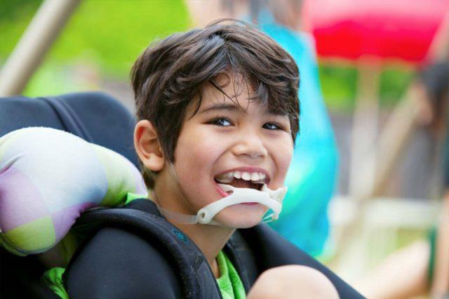Descrição da imagem #PraTodosVerem: Imagem no formato retangular, na horizontal. Um menino que tem paralisia cerebral está sentado em sua cadeira de rodas. Ele é moreno, tem a pele clara e cabelos castanhos, lisos e curtos. O menino está sorrindo. Fim da descrição.