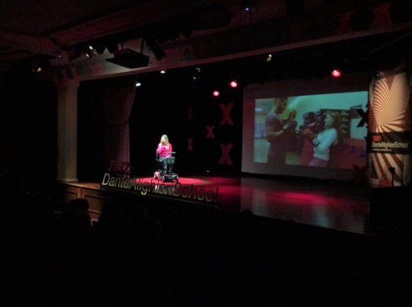 Foto da Nathalia Blagevitch sentada em uma scooter em um palco. Ela está em um auditório. Ao fundo, há um telão que mostra Nathalia usando luvas de boxe, em pé, na frente de um homem que também está usando luvas de boxe.