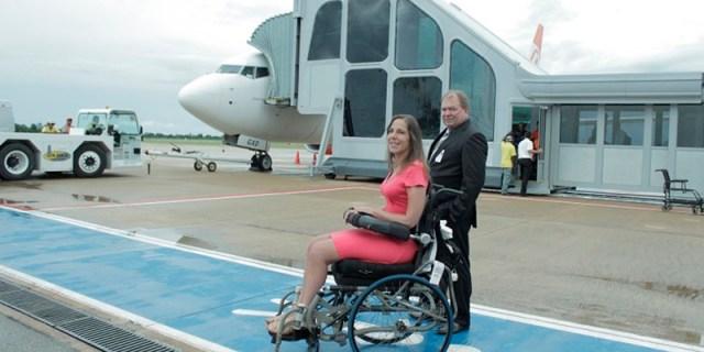 Mara, na pista do aeroporto, próximo ao avião estacionado no finger. Ao seu lado está um homem.