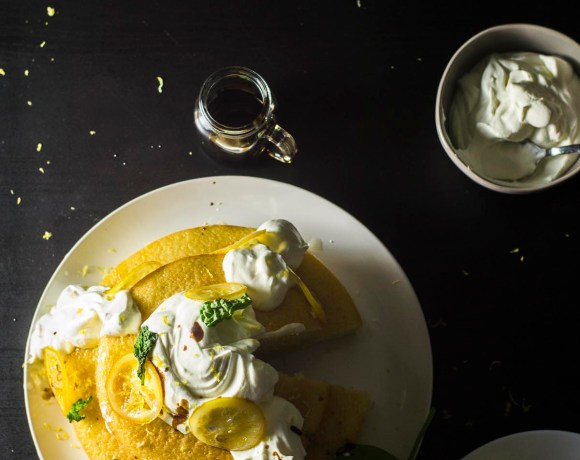 Overview of Lemon Basil Cake with a bowl of whipped cream and a bottle of balsamic reduction