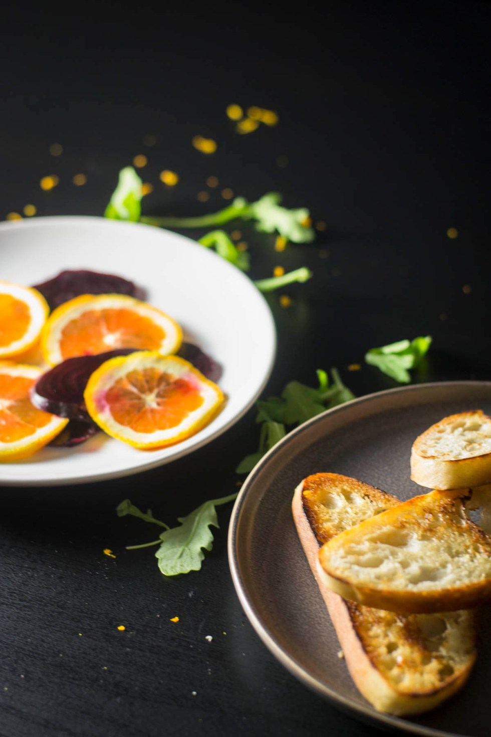 Sliced oranges and toast on plates